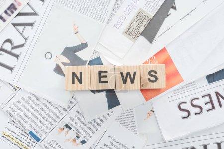 Photo pour Vue de dessus des cubes en bois avec des nouvelles de mot sur les journaux - image libre de droit