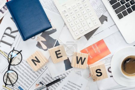 top view of wooden cubes with word news, laptop and calculator on newspapers