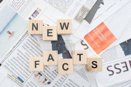 Photo pour Vue de dessus des cubes en bois avec des mots faits nouveaux sur les journaux - image libre de droit