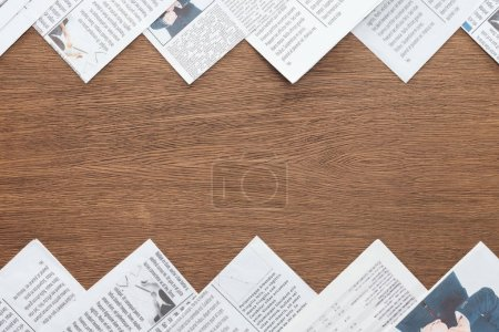 top view of different newspapers on wooden tabletop