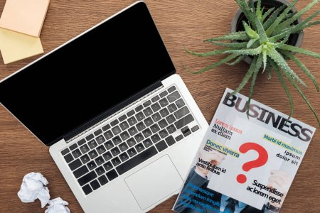 Photo for Top view of laptop, business magazine and potted plant on wooden tabletop - Royalty Free Image