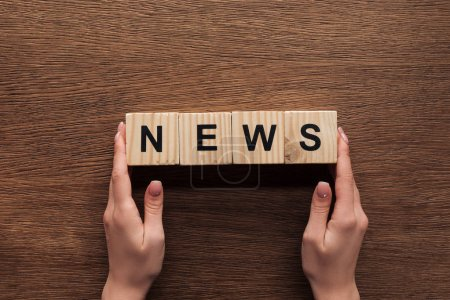Photo for Cropped image of journalist holding wooden cubes with word news at wooden table - Royalty Free Image