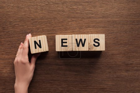 Photo for Cropped image of journalist taking wooden cubes with word news at wooden table - Royalty Free Image