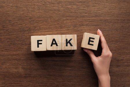 Foto de Recortar imagen de periodista teniendo cubos de madera con la palabra falso en la mesa de madera - Imagen libre de derechos