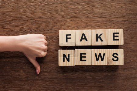 Photo for Cropped image of journalist showing thumb down to wooden cubes with words fake news at wooden table - Royalty Free Image