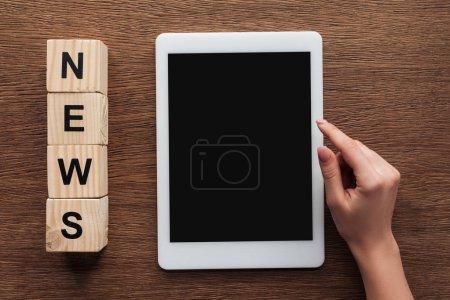 Foto de Imagen recortada del periodista utilizando tablet con la pantalla en blanco, cubos de madera con noticias palabra sobre mesa de madera - Imagen libre de derechos