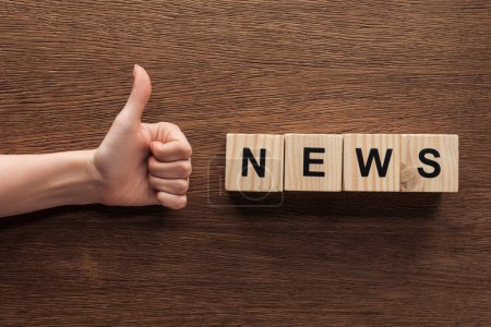 cropped image of journalist showing thumb up to wooden cubes with word news at wooden table