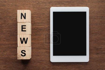 Foto de Vista superior de la tableta con pantalla en blanco y cubos de madera con noticias de la palabra en la mesa de madera - Imagen libre de derechos