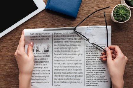 cropped image of journalist holding newspaper and glasses at wooden table