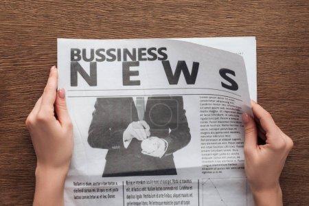 Photo pour Image recadrée de journaliste en lisant le journal d'affaires à table en bois - image libre de droit