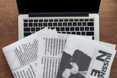 Photo pour Vue de dessus des journaux et l'ordinateur portable sur une table en bois - image libre de droit