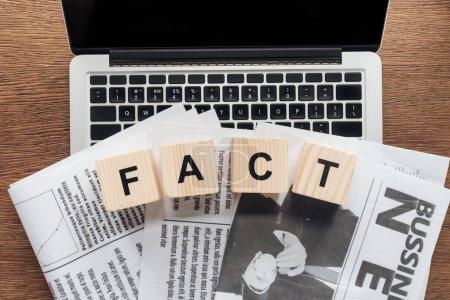 Photo pour Vue de dessus des cubes en bois avec le fait de mot et les journaux sur l'ordinateur portable sur la table en bois - image libre de droit