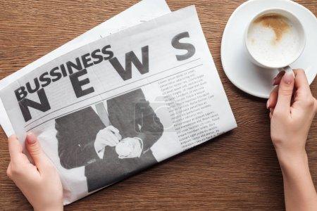 Photo pour Image recadrée de journaliste tenant le journal d'affaires et de la tasse de café à une table en bois - image libre de droit