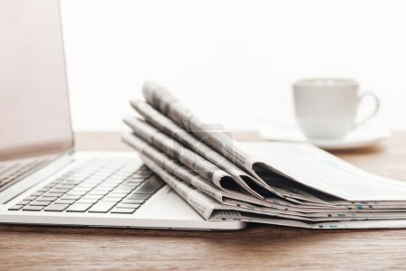 laptop, cup of coffee and stack of newspapers on wooden tabletop