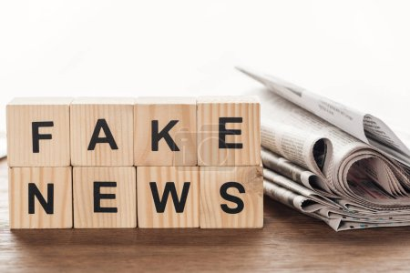 Photo for Wooden cubes with words fake news and newspapers on wooden tabletop - Royalty Free Image