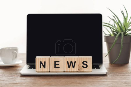 Photo for Wooden cubes with word news on laptop with blank screen on wooden tabletop - Royalty Free Image