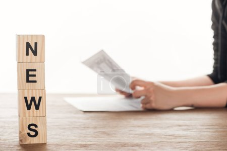 Photo for Cropped image of journalist reading newspaper, wooden cubes with word news on wooden table - Royalty Free Image