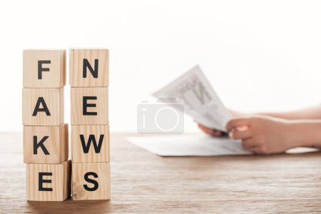 Photo for Cropped image of journalist reading newspaper, wooden cubes with words fake news at wooden table - Royalty Free Image