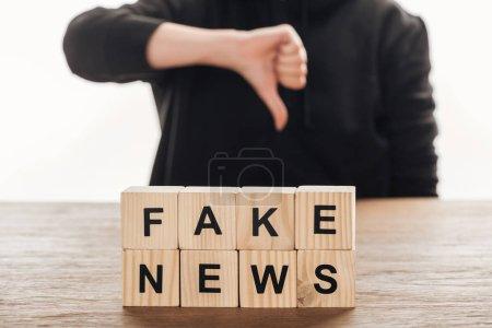 Photo pour Cropped image du journaliste montrant le pouce vers le bas pour des cubes en bois avec des mots nouvelles fausses à table en bois - image libre de droit
