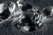 close up of transparent diamonds on grey textured background