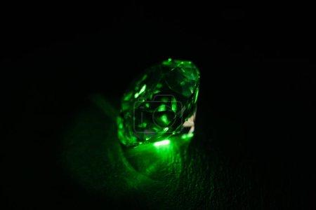 Foto de Diamantes iluminados con luz de neon verde brillante sobre fondo oscuro - Imagen libre de derechos