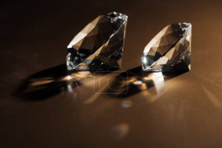 sparkling clear diamonds on brown background with copy space