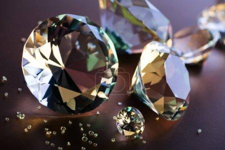 Photo pour Gros plan des grands et petits diamants sur fond marron - image libre de droit