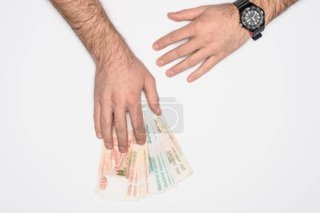 partial view of man holding Russian rubles isolated on grey