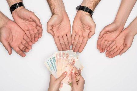 Photo pour Vue recadrée de femme donnant le groupe de personnes les billets russes isolés sur fond gris - image libre de droit
