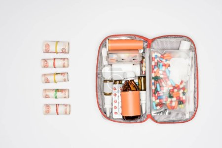 top view of money rolls and first aid kit with medicine isolated on grey