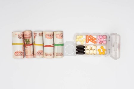 top view of money rolls and pills in plastic container isolated on grey