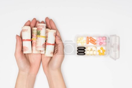 cropped view of woman holding money rolls in hands near plastic container with pills isolated on grey