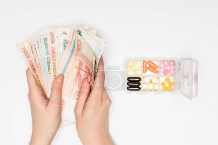cropped view of woman counting russian roubles near pills in box isolated on grey