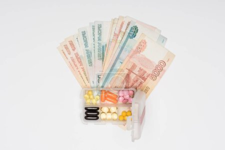 top view of cash and plastic box with pills isolated on grey