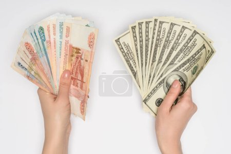 cropped view of woman holding russian rubles and dollars in hands isolated on grey