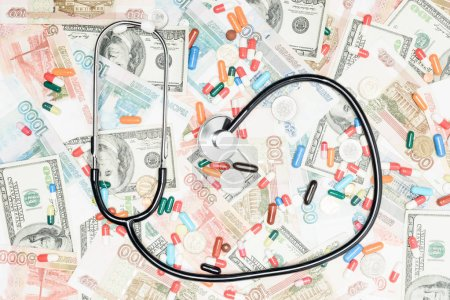 top view of multicolored pills, coins and stethoscope on money background
