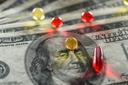 close up of bright oval and round pills on dollars background