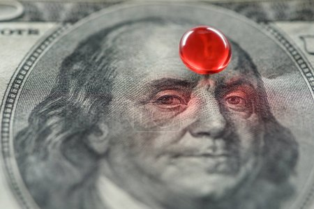 close up of shiny red round pill on dollar banknote