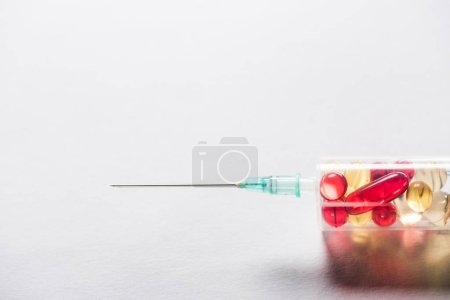 Photo for Close up of syringe with red and yellow pills on grey background - Royalty Free Image