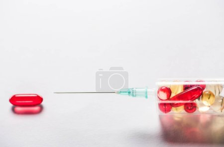 close up of syringe with medication near red oval pill on grey background