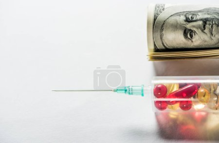 close up of syringe with medication near money roll on grey background