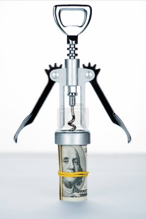 corkscrew with money roll on blurred white and grey background