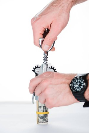 cropped view of man using corkscrew with money roll on blurred white and grey background
