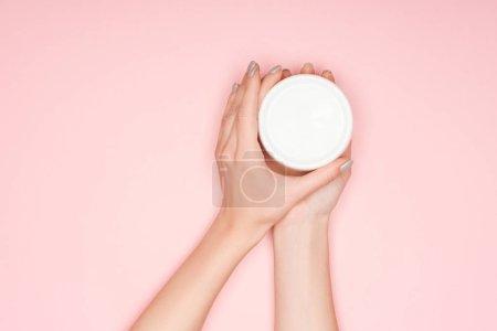 vista parcial de las manos femeninas con crema corporal aislada en rosa