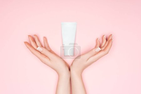 Photo pour Vue recadrée des mains féminines avec crème pour les mains isolée sur rose - image libre de droit