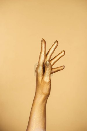 Photo for Cropped view of female painted hand isolated on gold - Royalty Free Image