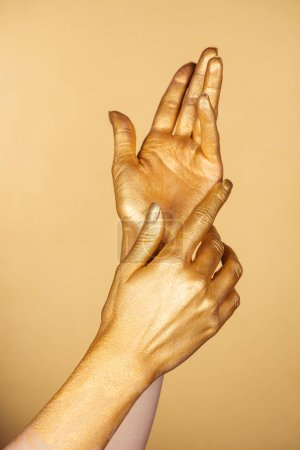 cropped view of female painted hands isolated on gold