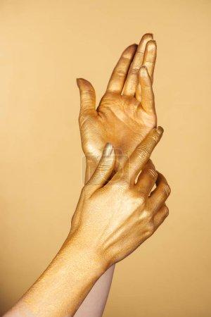 vista recortada de manos pintadas femeninas aisladas en oro