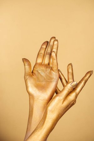 partial view of female painted hands isolated on gold