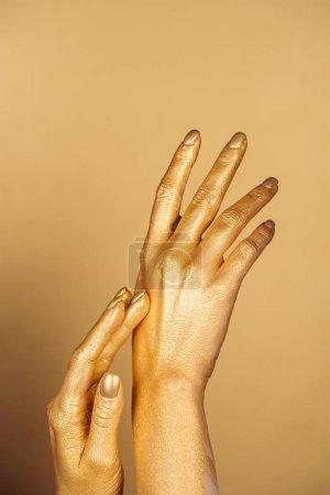 vista recortada de manos pintadas femeninas sobre fondo dorado